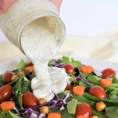 Pouring dressing on a salad