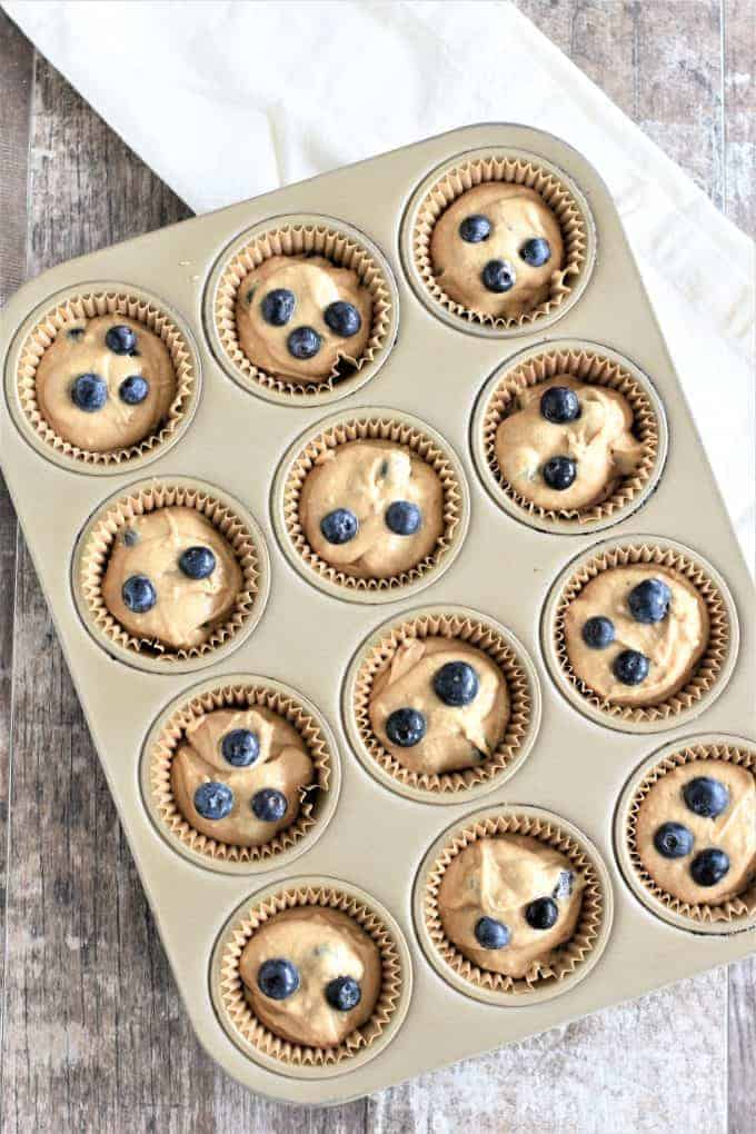 Baking cups filled with batter in a muffin pan