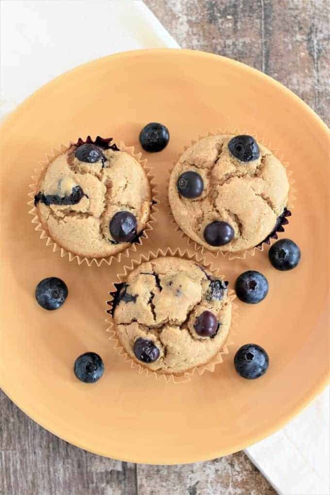 Vegan Blueberry Muffins on a plate with blueberries