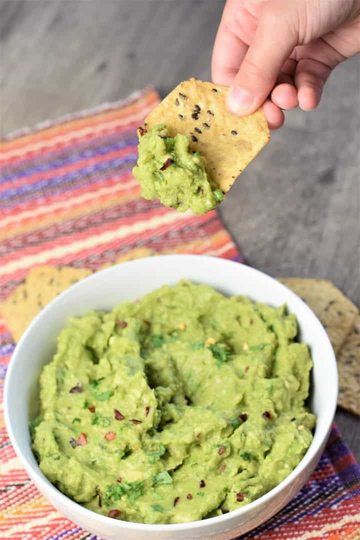 Guacamole being scooped with a chip
