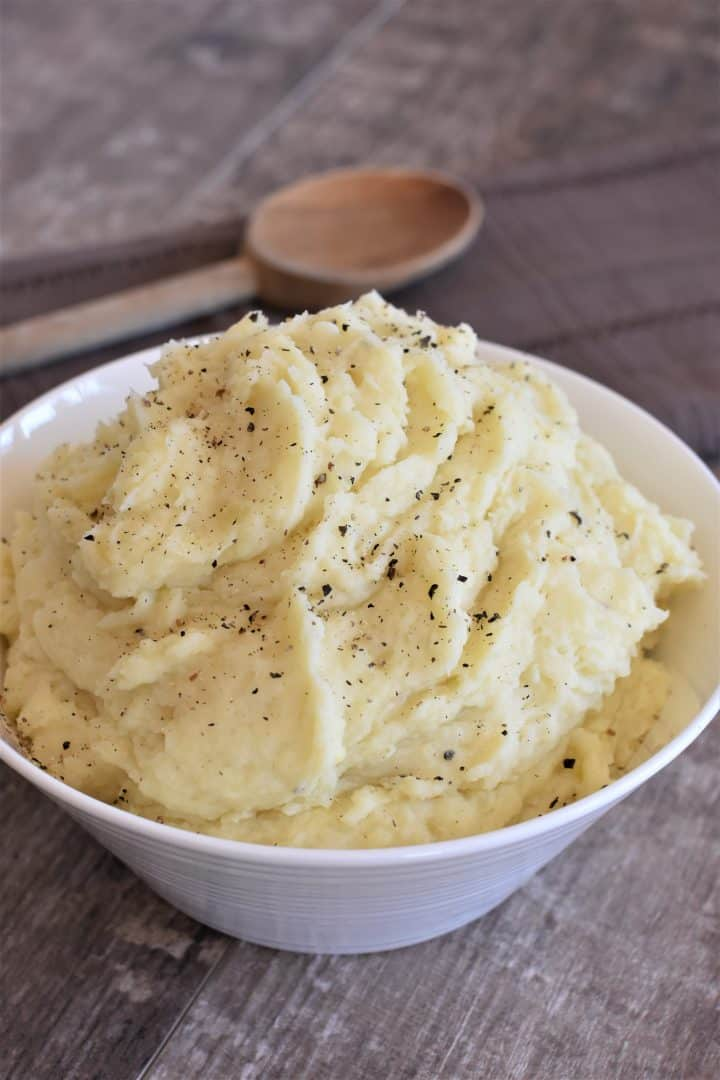 front view of mashed potatoes in a white bowl with wooden spoon behind them