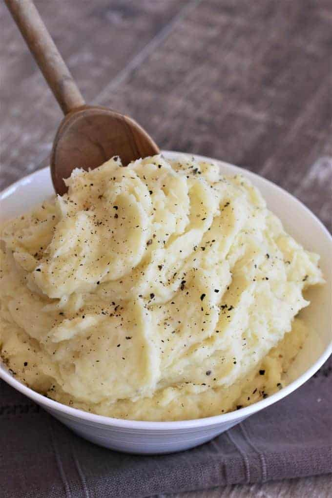 mashed potatoes in a white bowl with a wooden spoon dipping in
