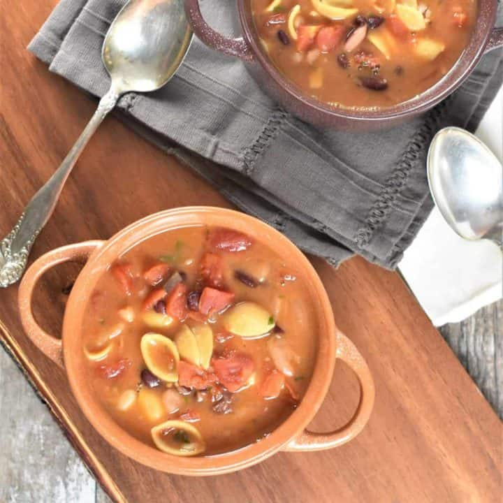 overhead of two bowls of soup on wooden board and kitchen napkins with spoons next to them