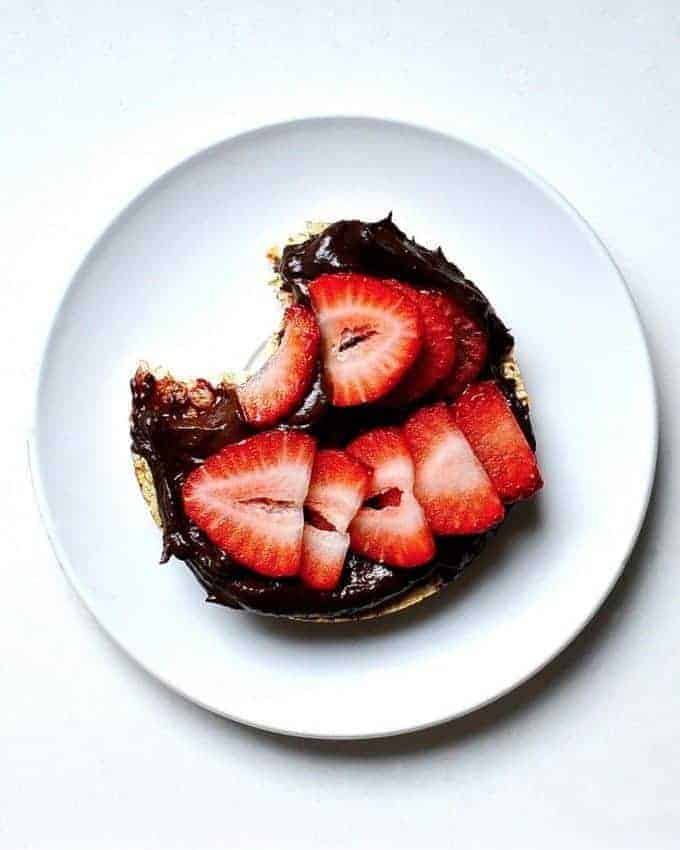 Vegan nutella on a bagel with strawberries on top
