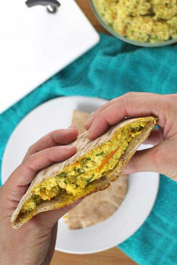 Hands holding half of a pita with tofu egg salad