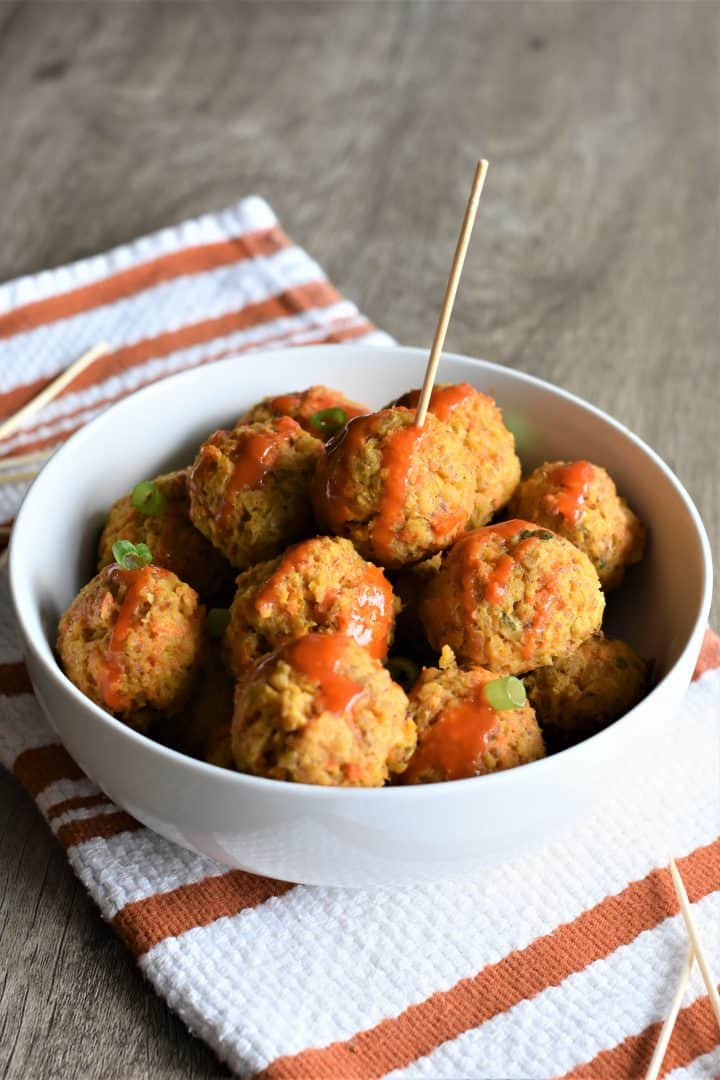 side view of chickpea balls in a white bowl, one with a toothpick in it