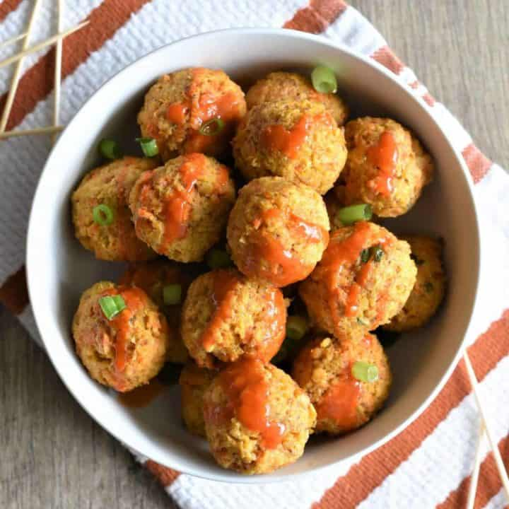 overhead of chickpea balls topped with Buffalo sauce and scallions in white bowl