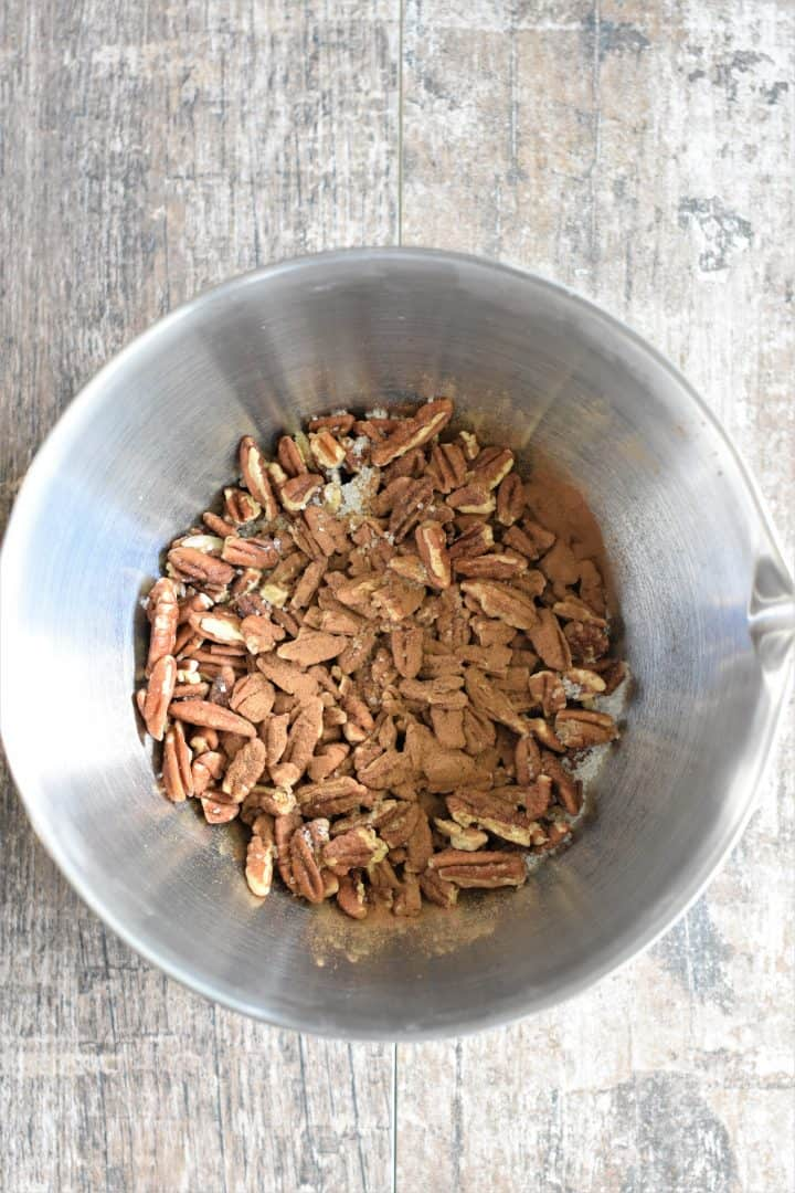 Cinnamon, maple syrup and salt added to the raw pecans in a mixing bowl