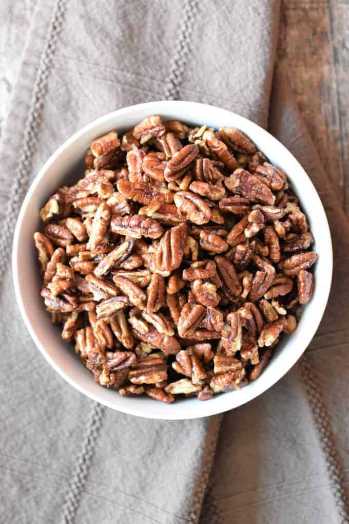 overhead shot of roasted pecans in a white bowl