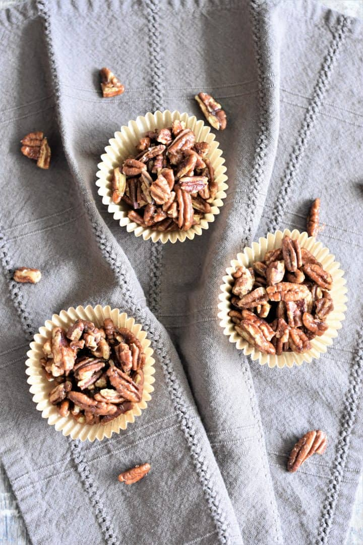 pecans in three parchment baking cups on a kitchen towel with more pecans sprinkled on the towel