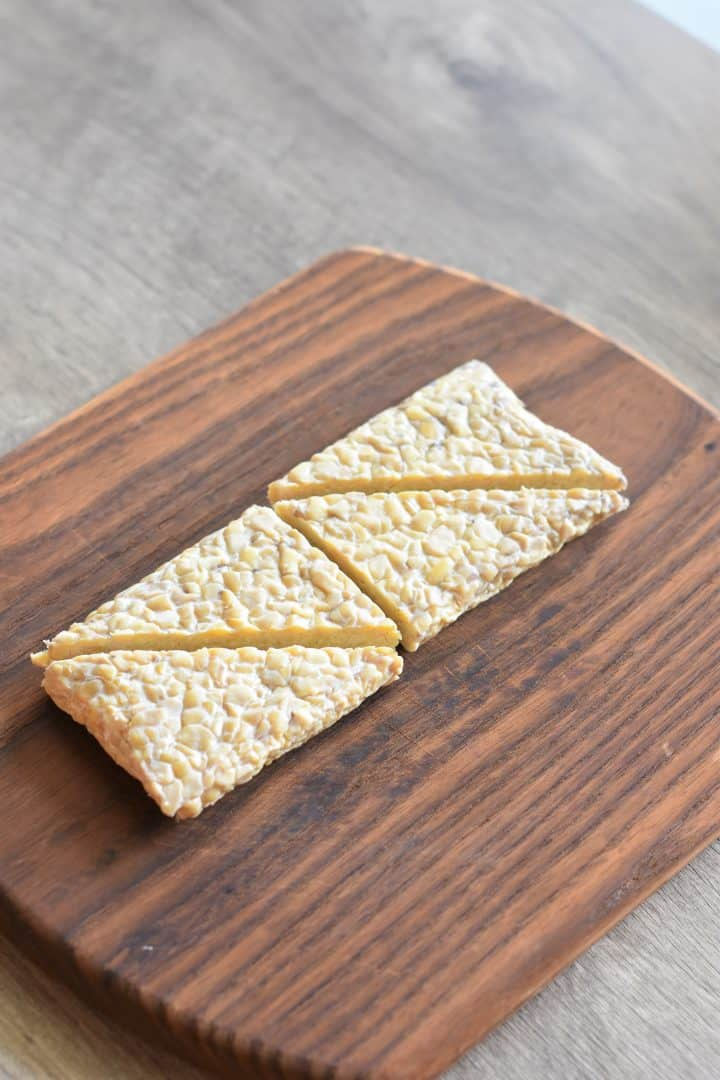 tempeh cut into triangles on a cutting board