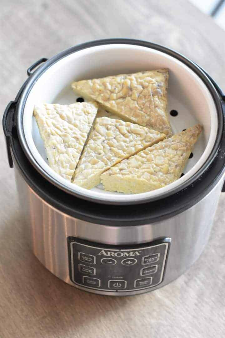 tempeh triangles added to steamer basket in a rice cooker