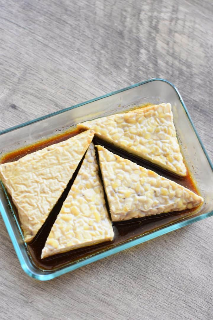 tempeh triangles added to marinade in glass dish