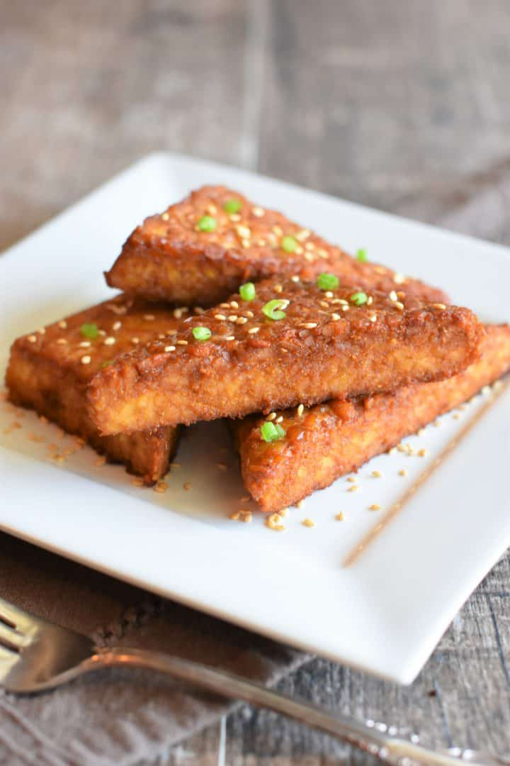 Baked tempeh on a dish garnished with toasted sesame seeds and scallions