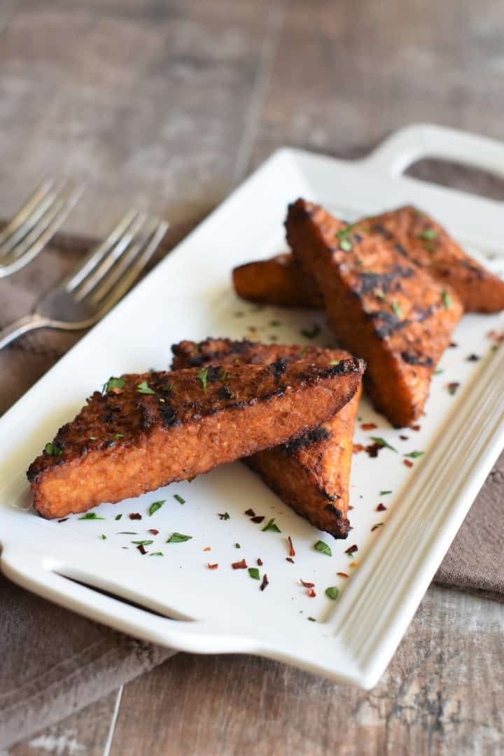 grilled tempeh on a white platter garnished with fresh parsley and red pepper flakes