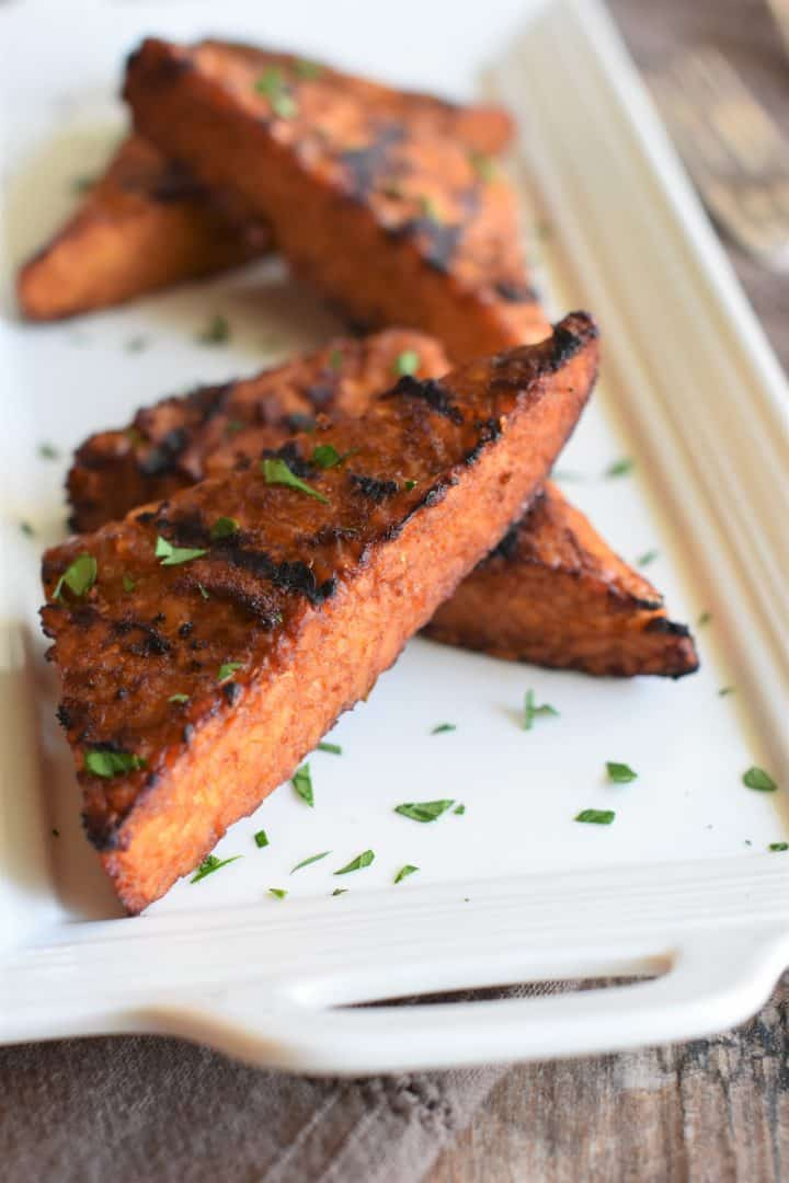 Close up view of grilled tempeh on a white platter garnished with parsley