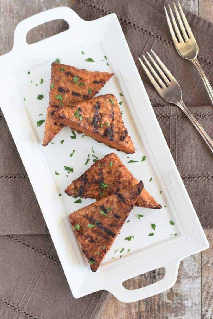 overhead view of grilled tempeh garnished with parsley on a white platter