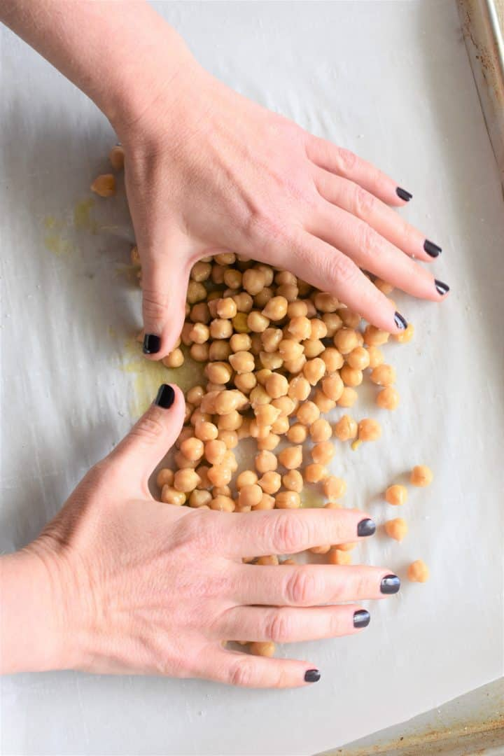 Coating chickpeas with oil and salt using hands