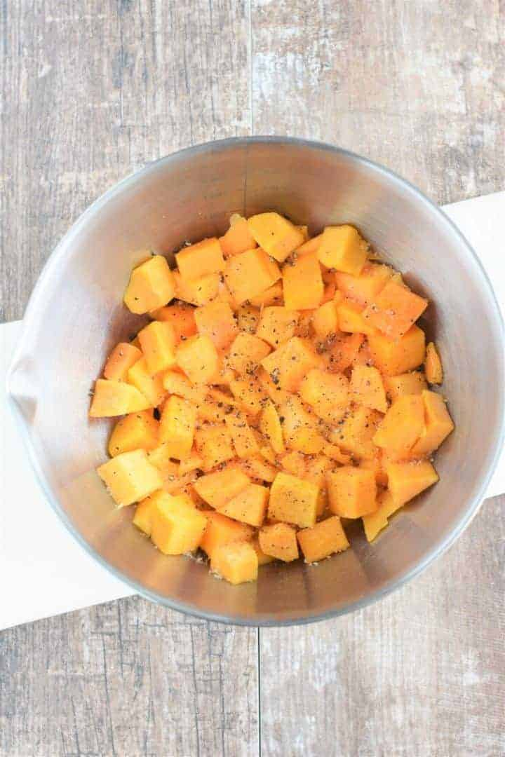 Olive oil, salt and pepper added to butternut squash chunks in mixing bowl