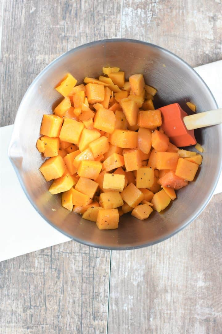 Stirring the butternut squash to evenly coat with olive oil, salt and pepper