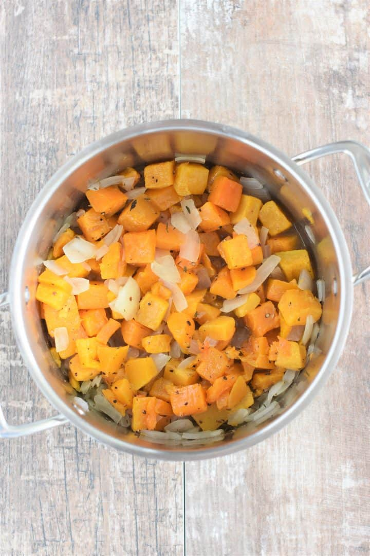 Seasonings and butternut squash added to soup pot