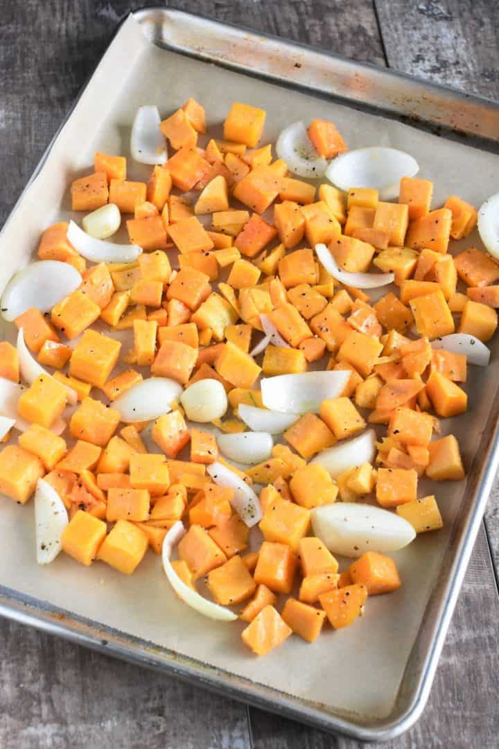 Seasoned butternut squash, onion and garlic on a baking sheet ready to be cooked