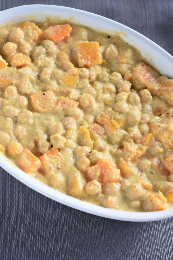 Sauce mixed into chickpeas and butternut squash in casserole dish