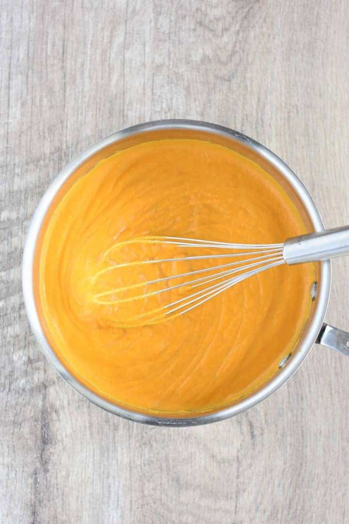 whisking the pumpkin mac and cheese sauce in saucepan