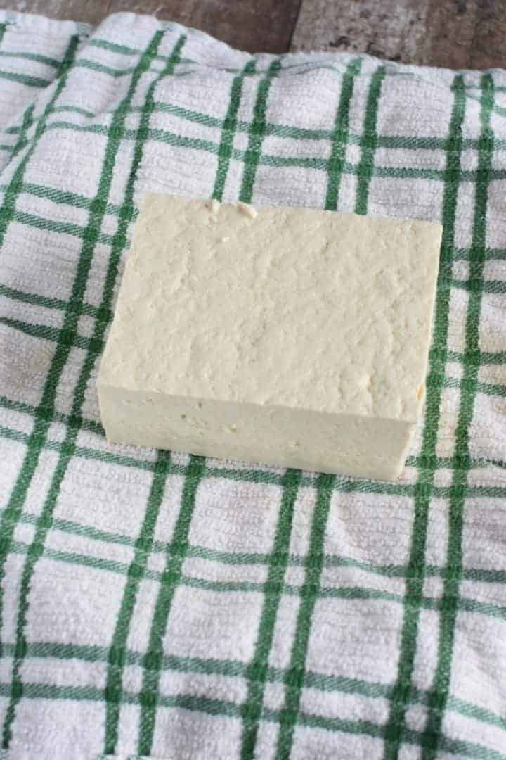 Tofu block placed in the center of a kitchen towel on a plate