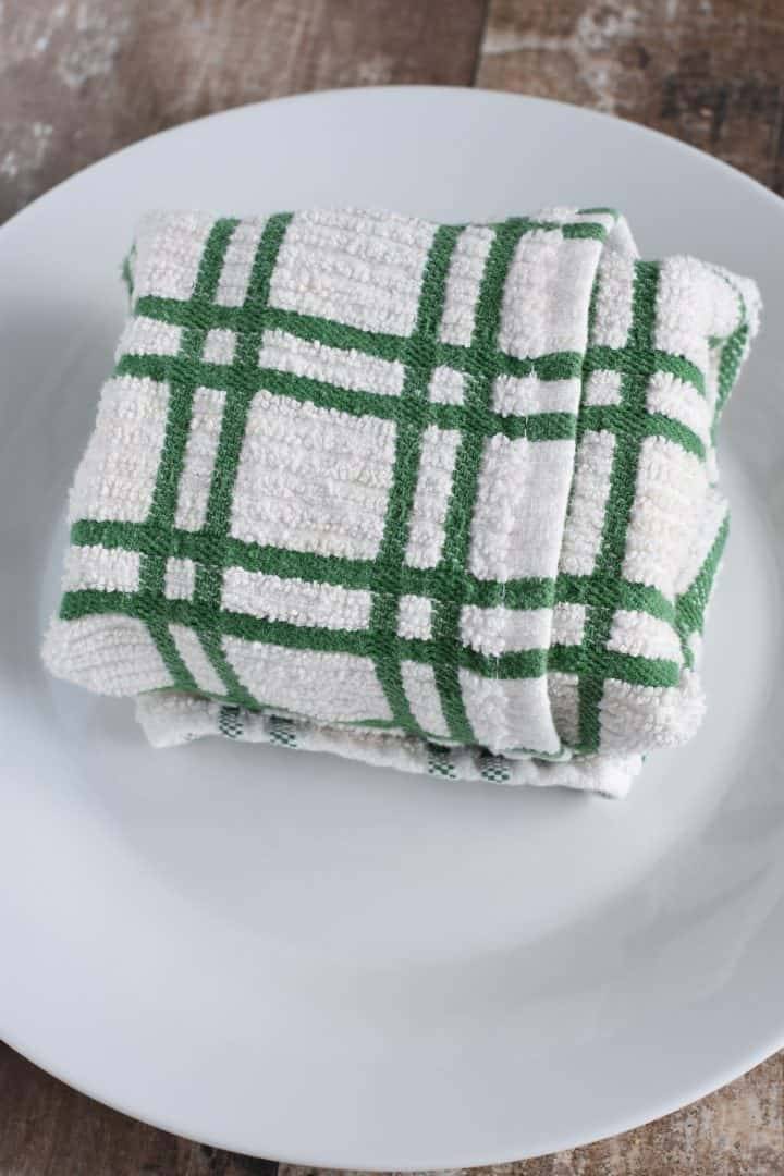 Tofu block wrapped in a towel on a plate