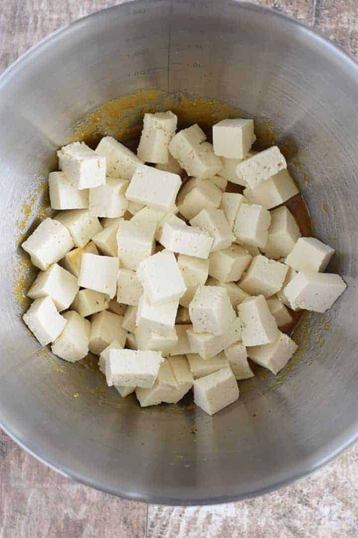 Tofu pieces added to the coating mixture in the mixing bowl