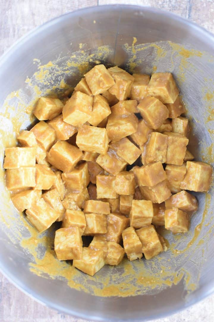 Tofu pieces coated with the sauce in the mixing bowl