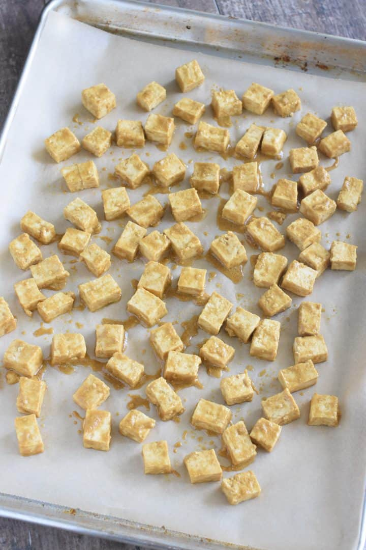 Tofu pieces spread out on a parchment-lined baking sheet