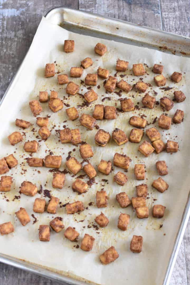 Tofu bites hot from the oven on the parchment-lined baking sheet