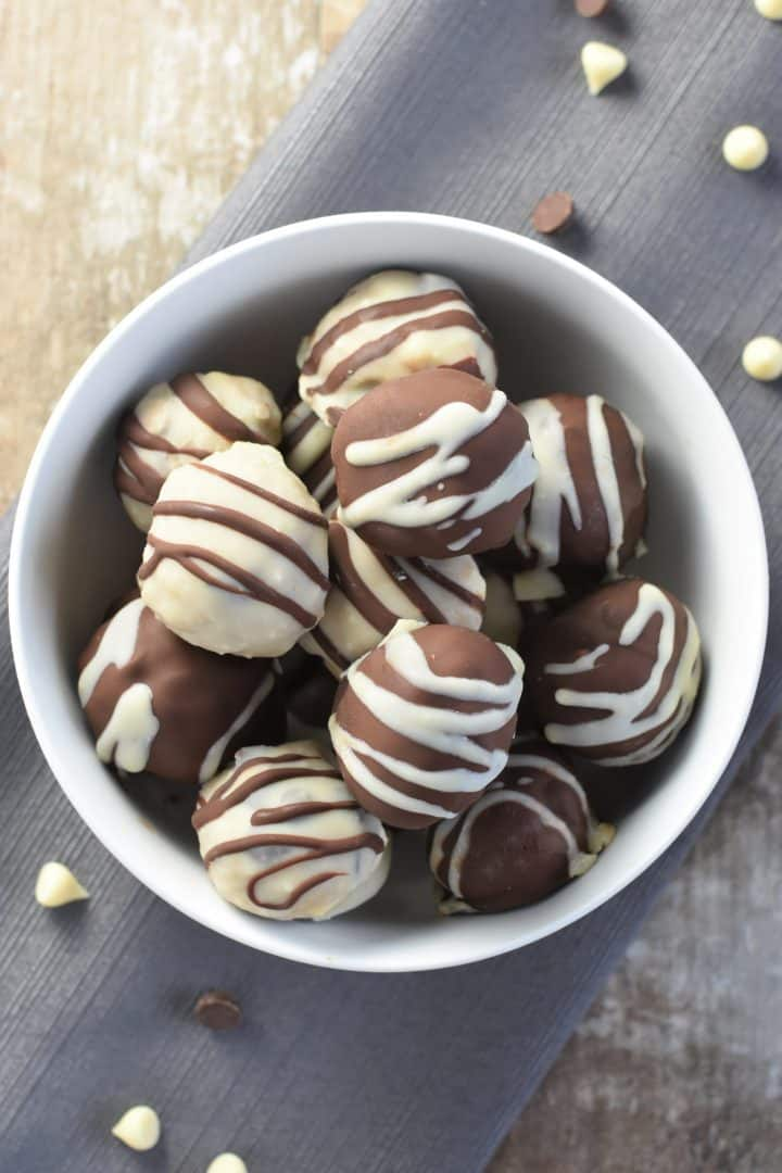 overhead shot of cookie dough truffles in a white bowl on a napkin with dark and white chips around it
