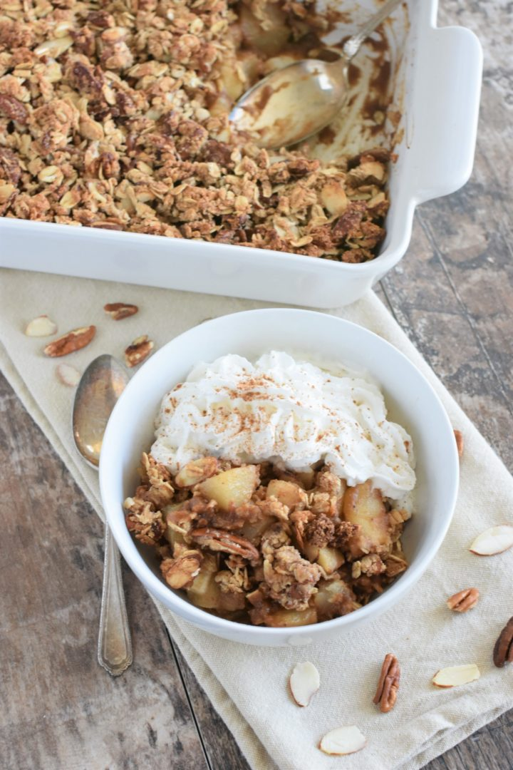 pear crisp in white bowl with coconut whipped topping and a spoon next to it with the rest in the baking dish in the background