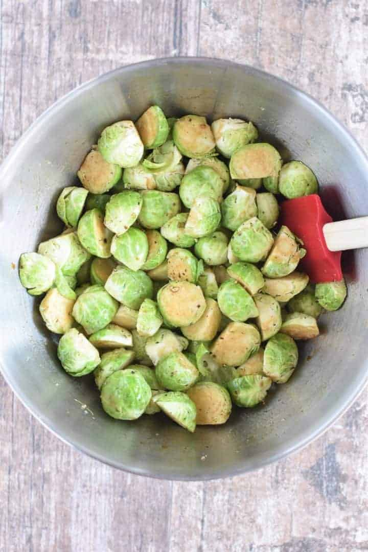 Brussels sprouts in mixing bowl with olive oil, balsamic vinegar, salt and pepper mixed in