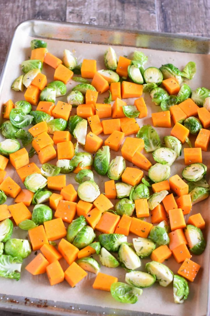 Butternut squash and Brussels sprouts spread out on baking sheet