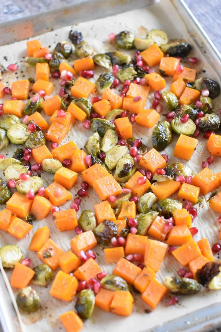 Pomegranate arils added to roasted butternut squash and Brussels sprouts on baking sheet