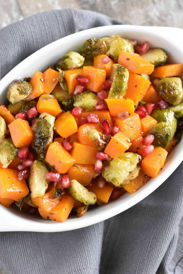 close up of butternut squash and Brussels sprouts with pomegranate arils in white serving dish