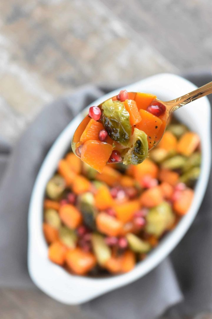 Spoonful of butternut squash and Brussels sprouts with pomegranate hovering over the rest in white serving dish