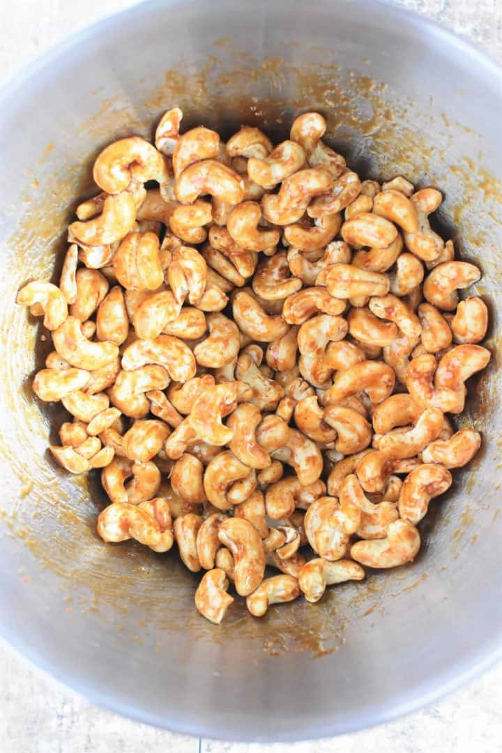 Date syrup, cayenne pepper and salt mixed into the cashews in a mixing bowl