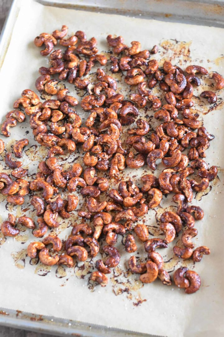Roasted cashews on baking sheet with sea salt sprinkled on top