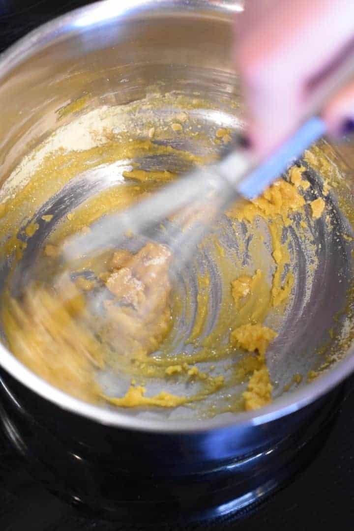 Whisking in chickpea flour to the vegan butter to make a roux