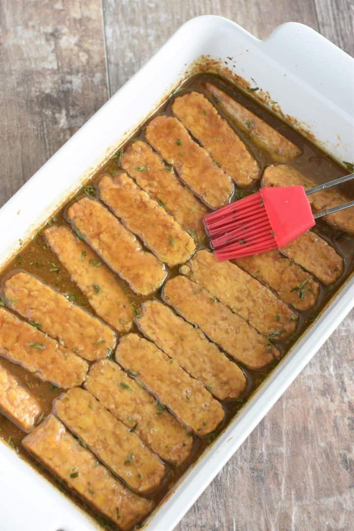 Basting the tempeh strips with a silicone pastry brush