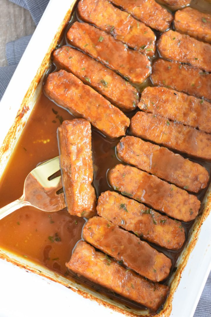 fork holding a piece of tempeh in the casserole dish with some missing