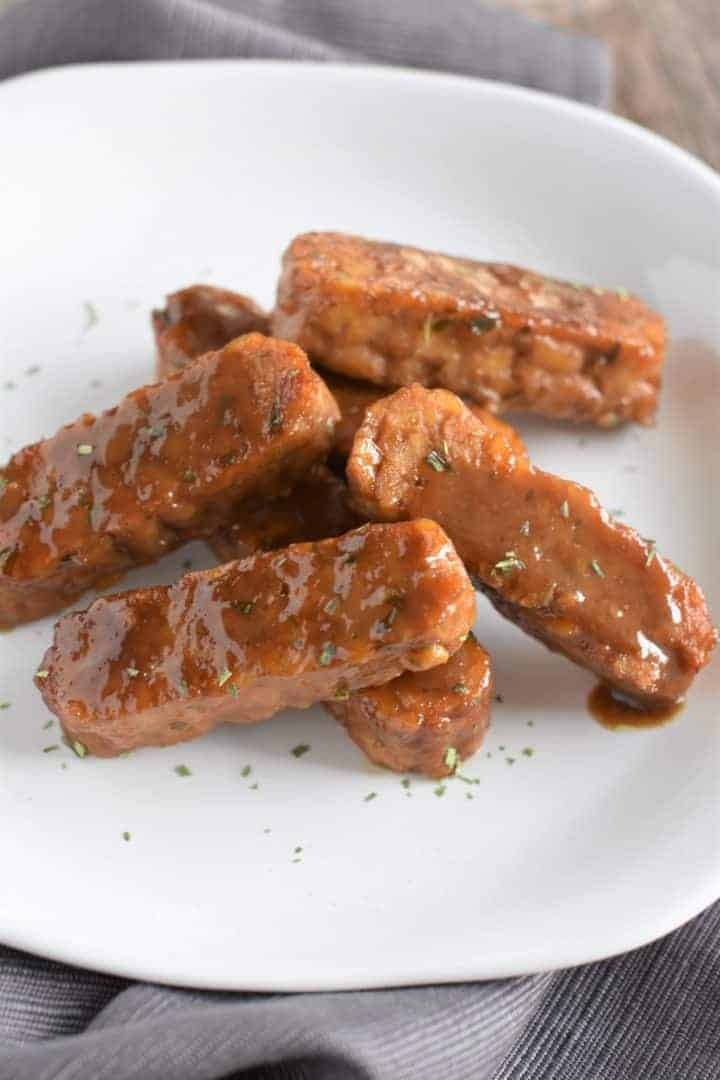 tempeh on white dish with extra tarragon ready to be served