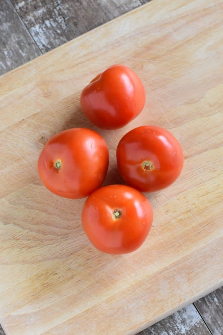 4 tomatoes on a cutting board