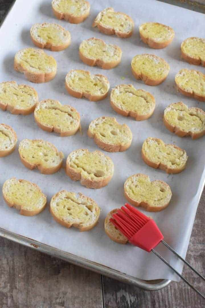 Brushing olive oil onto bread slices with silicone pastry brush on parchment-lined baking sheet