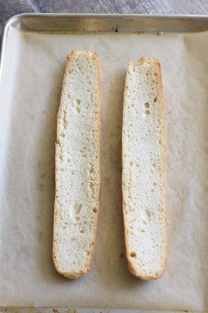 Lightly toasted bread halves on baking sheet